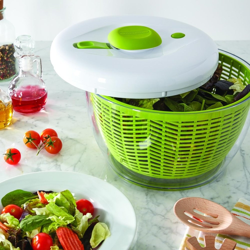 a salad spinner with a clear bowl, green colander, and white top next to a salad on a counter