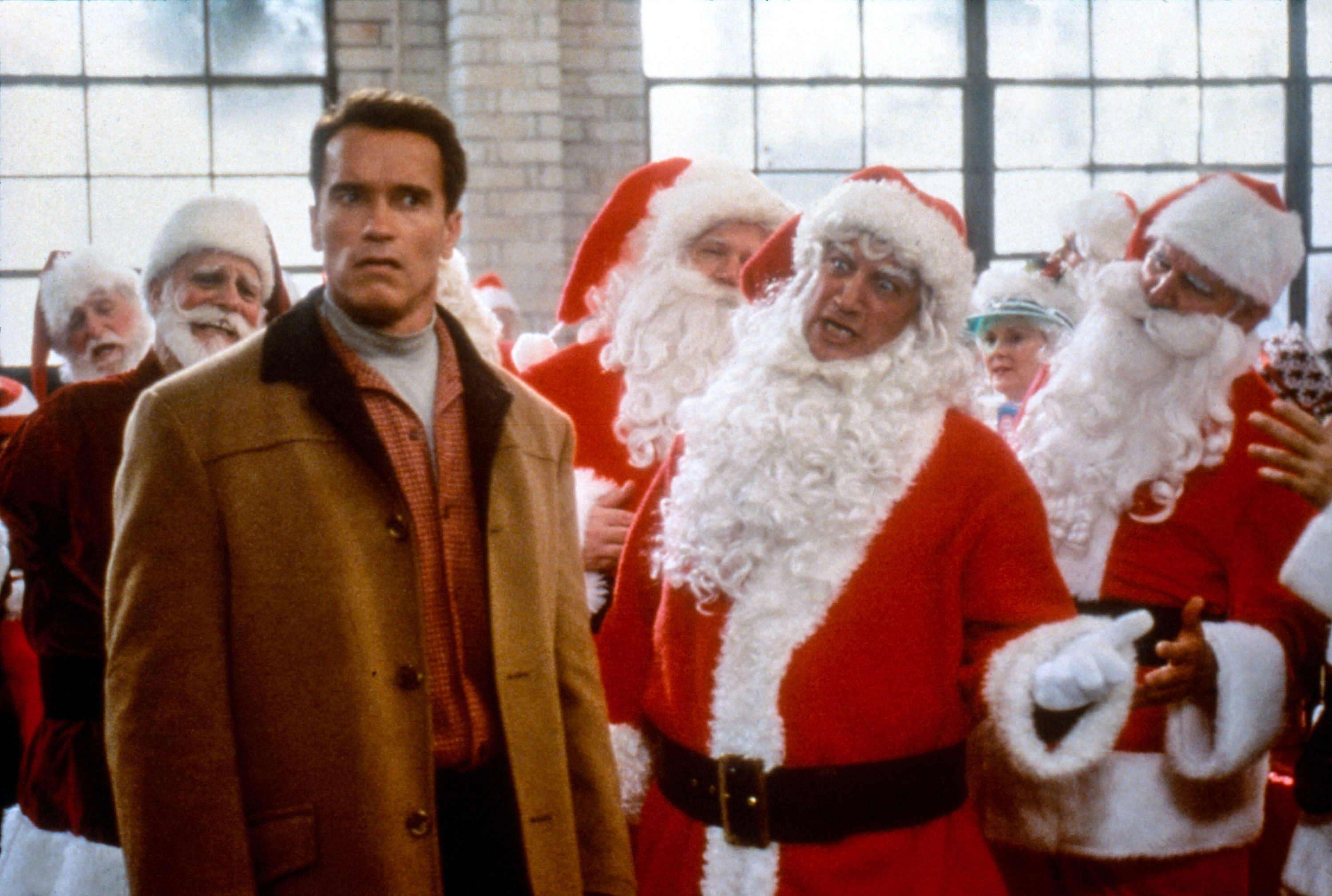 """Arnold Schwarzenegger as Howard Langston looks confused among several Santas in """"Jingle All the Way."""""""