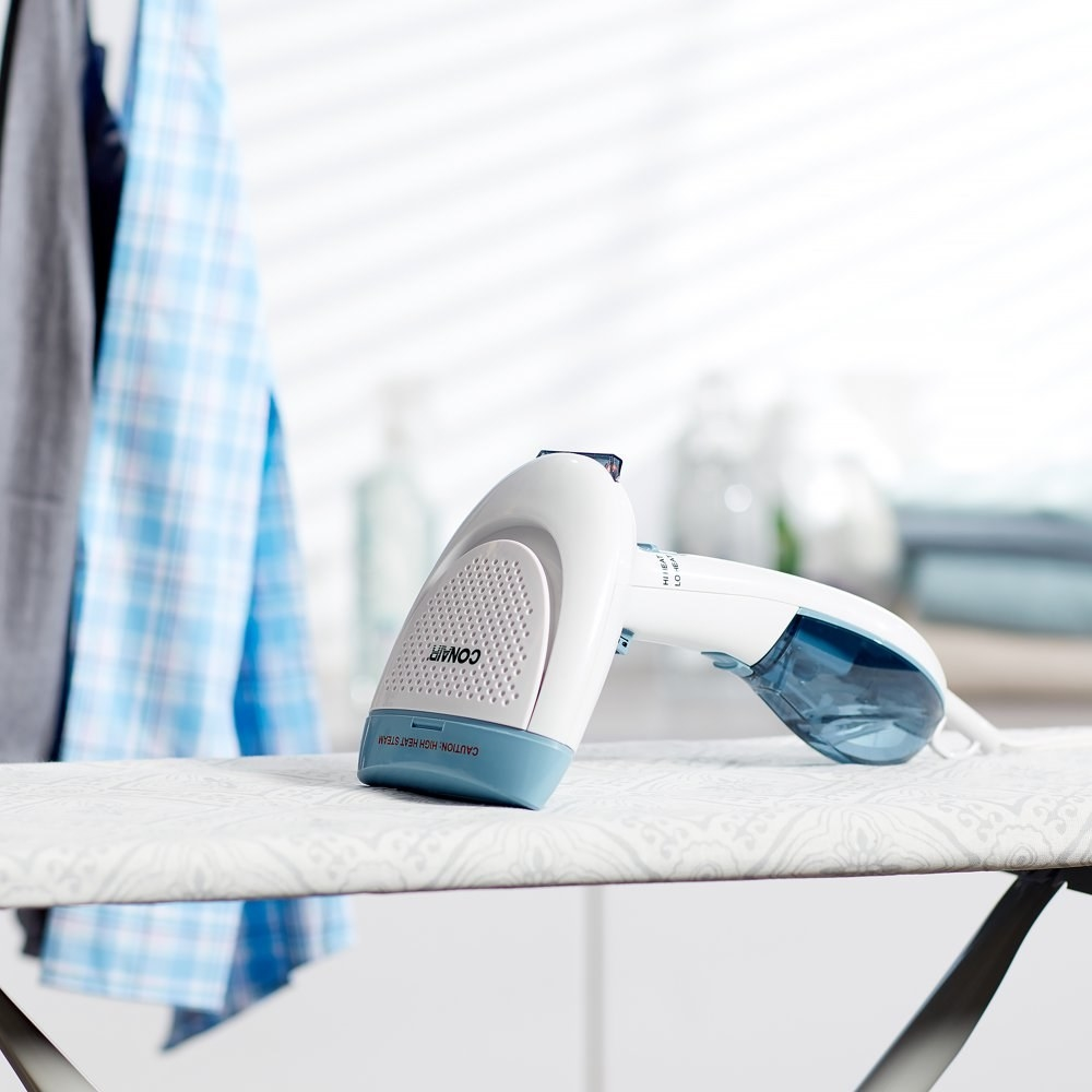 a blue and white conair steamer on an ironing board