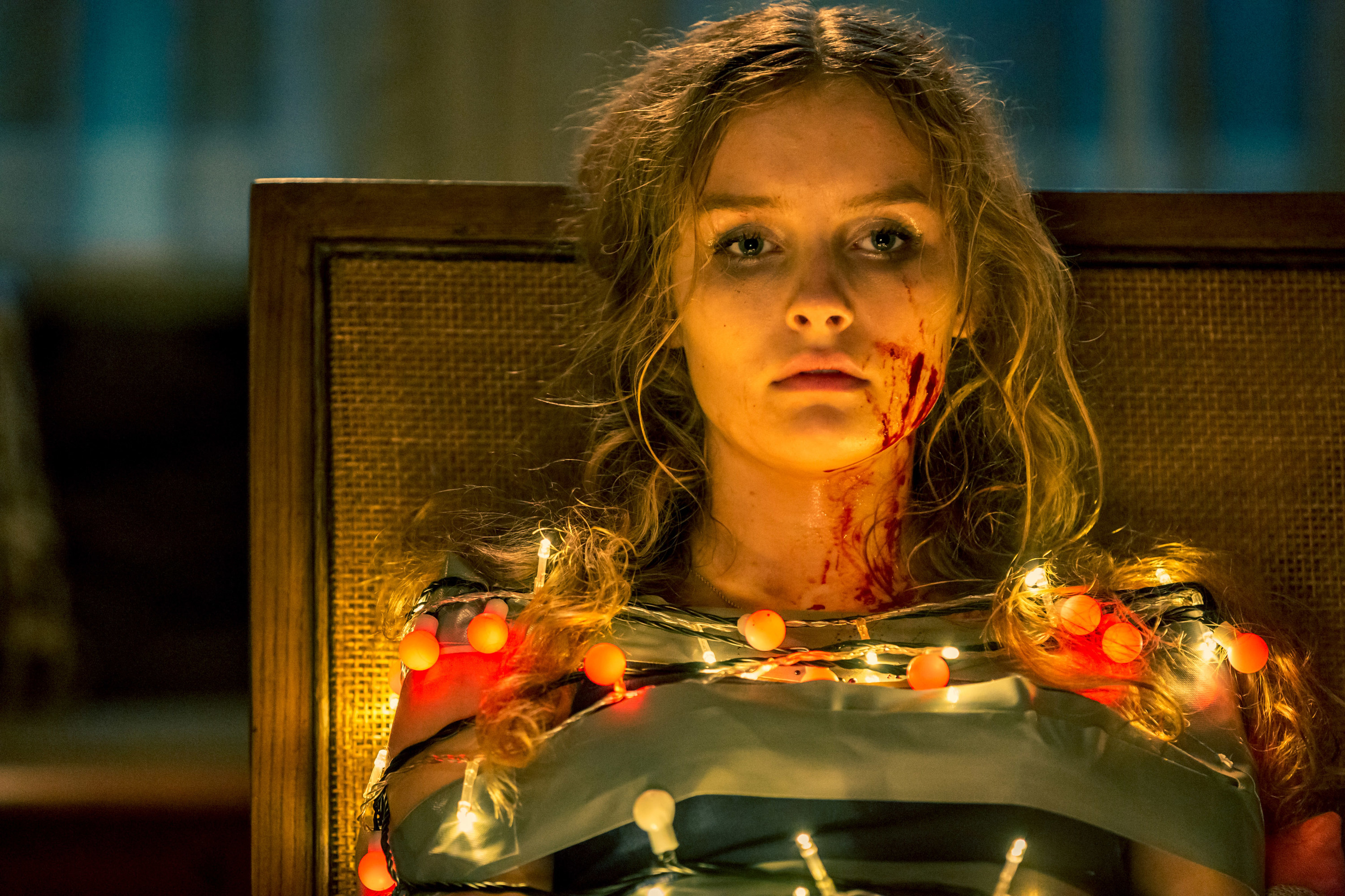 """A bloodied Olivia DeJonge tied to a chair with Christmas lights in """"Better Watch Out"""""""