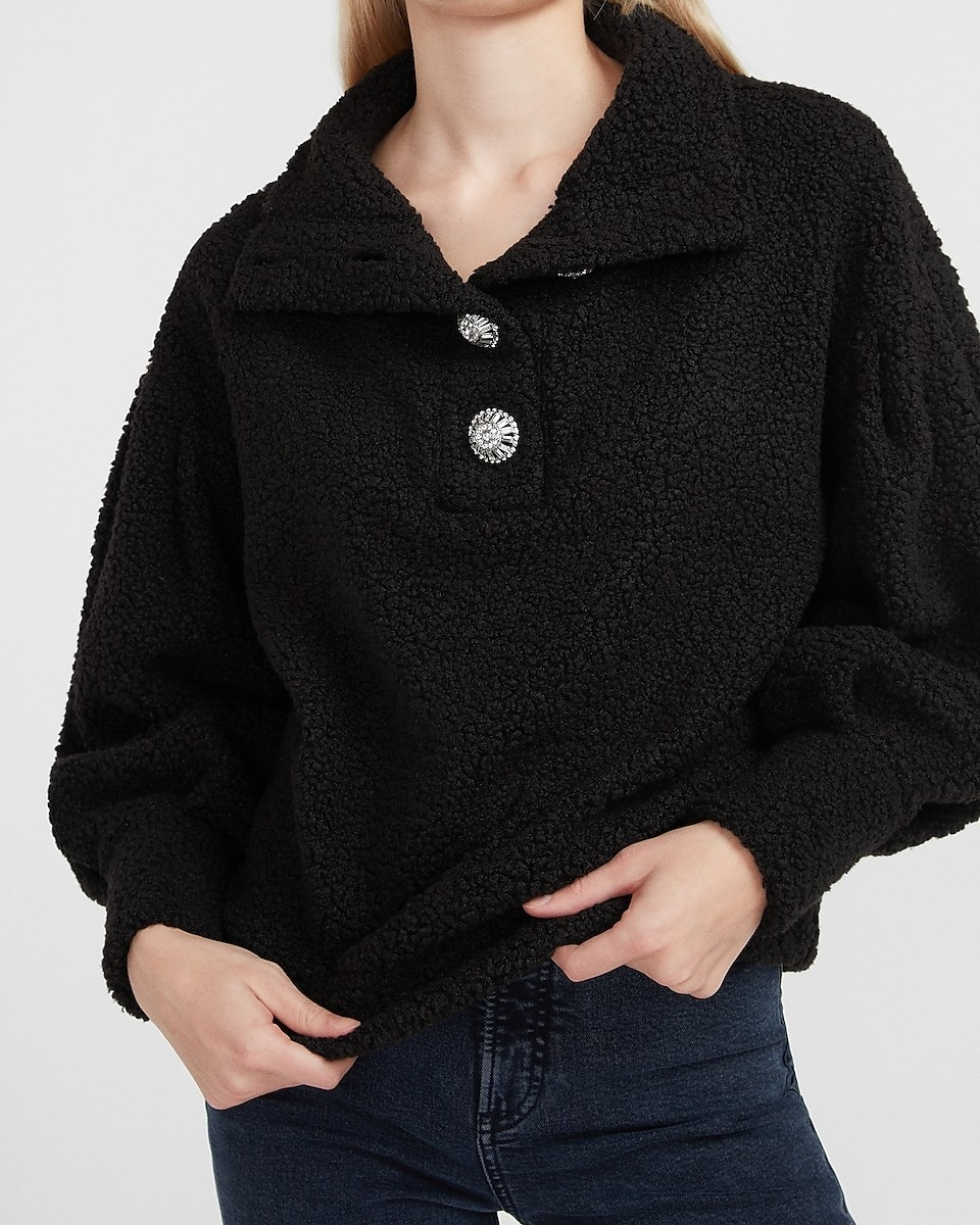 a model in a black sherpa pull over with oversized fancy buttons