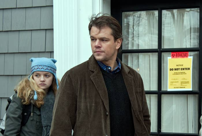"A still from the movie ""Contagion"" shows a blonde daughter in a scarf and knitted cap standing behind her father, in a corduroy jacket, both looking to their right; behind them is a ""biohazard: do not enter"" sign"