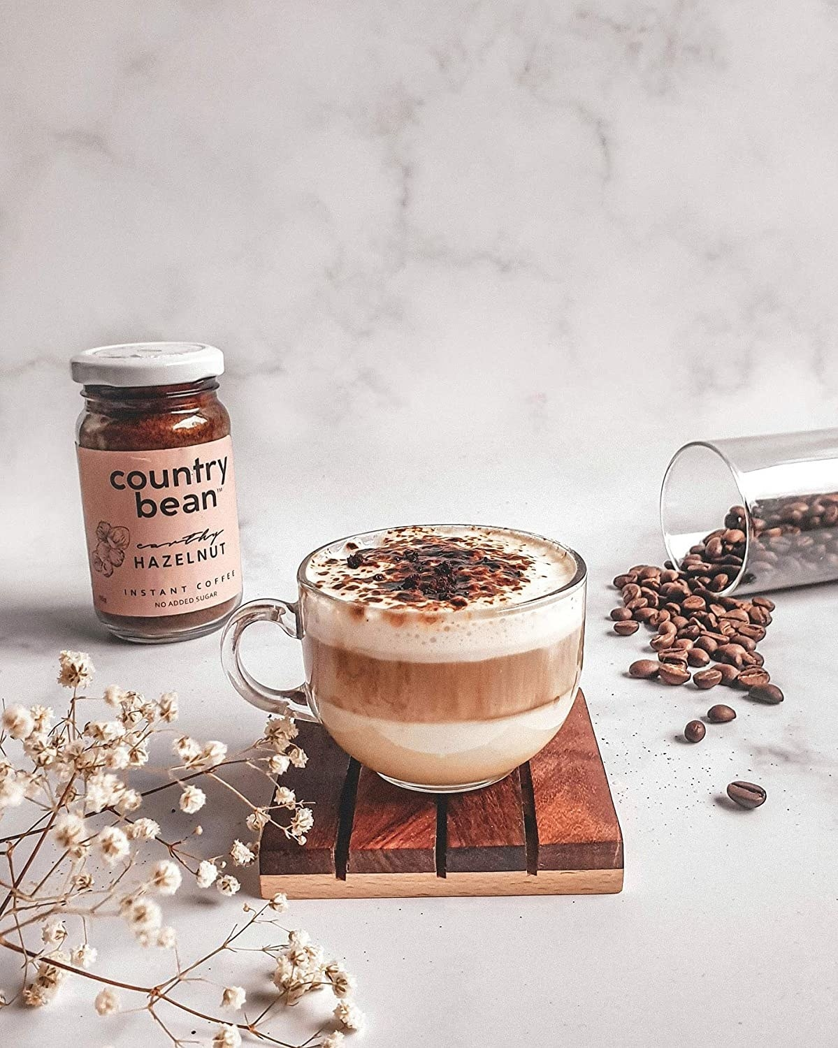 A mug of coffee kept on a wooden plank. There is a jar of spilling coffee beans in the background and sprig of white flowers in the front.