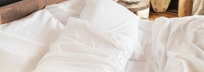 Pillows in white sheets on bed