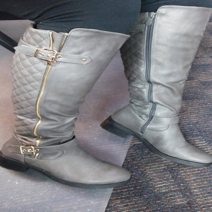 A reviewer wearing the boots in gray with gold hardware