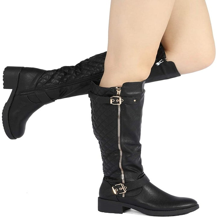 A model wearing the black boots with gold hardware