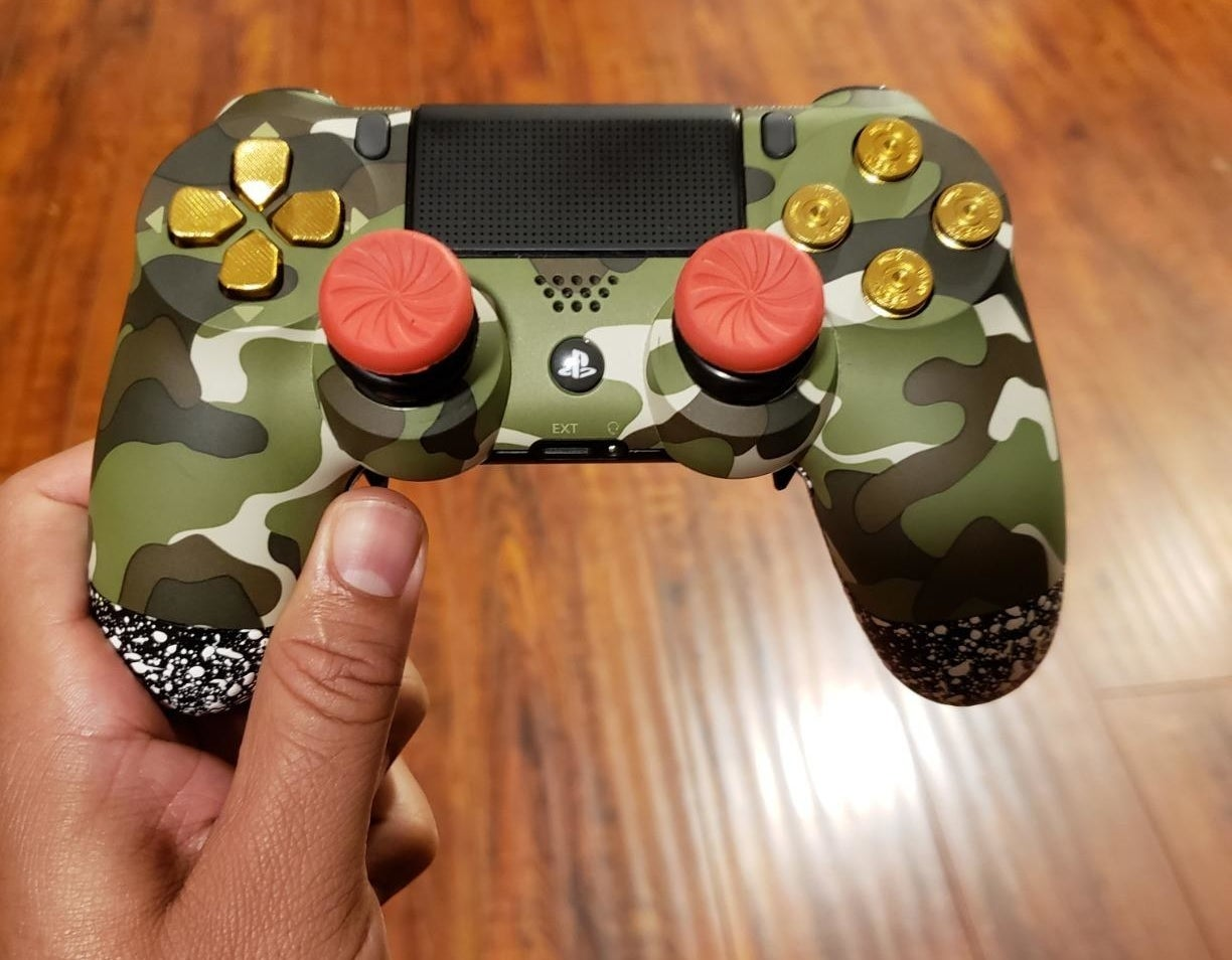 The red thumbsticks on a camo-print PS4 controller