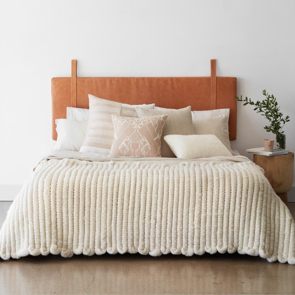 The tan leather headboard which hangs from two straps