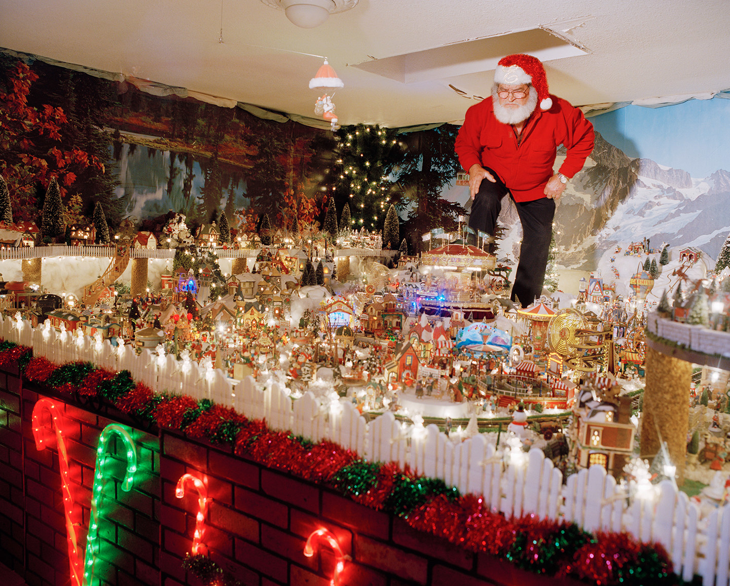 A man dressed as Santa stands above and peers over a miniature lit-up city display