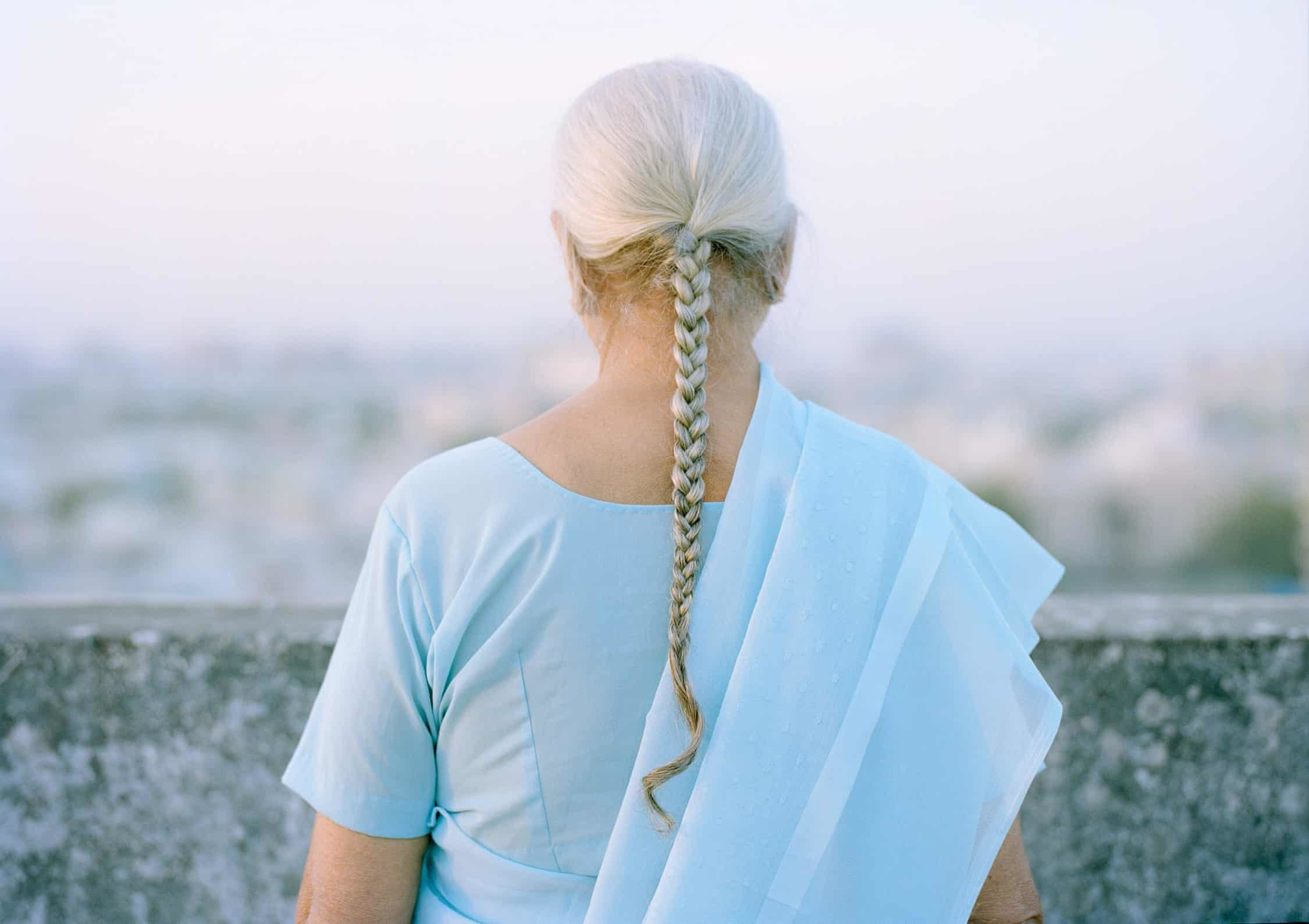 The back of a woman's head with braid turned to the camera