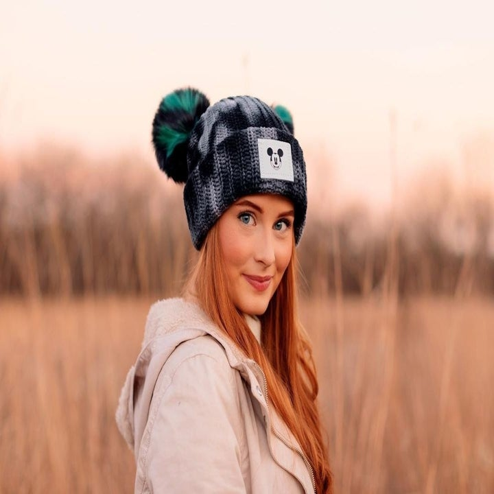 a model in a tie dye black and gray beanie with green and black pom poms