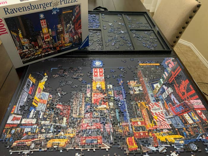 The puzzle board with portions of a completed puzzle on it and puzzle pieces in the sorting trays