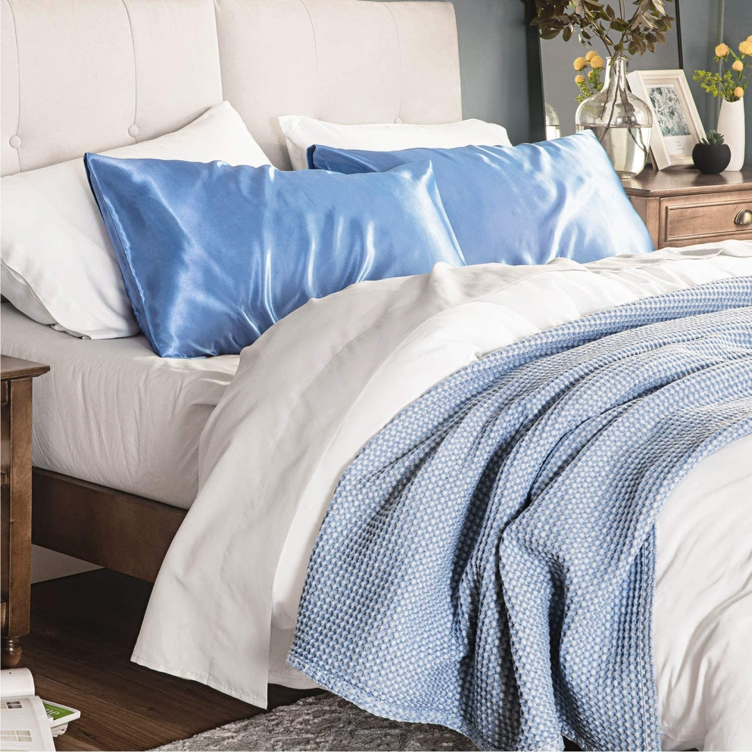 stock photo showing two blue satin pillowcases on a bed
