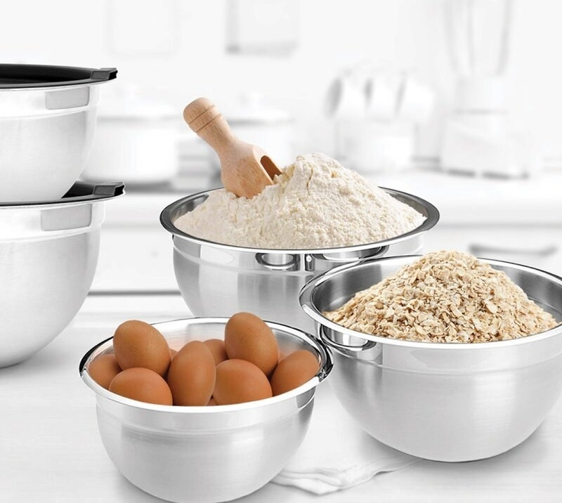 three whysko stainless steel bowls being used to store: flour, oats, and eggs
