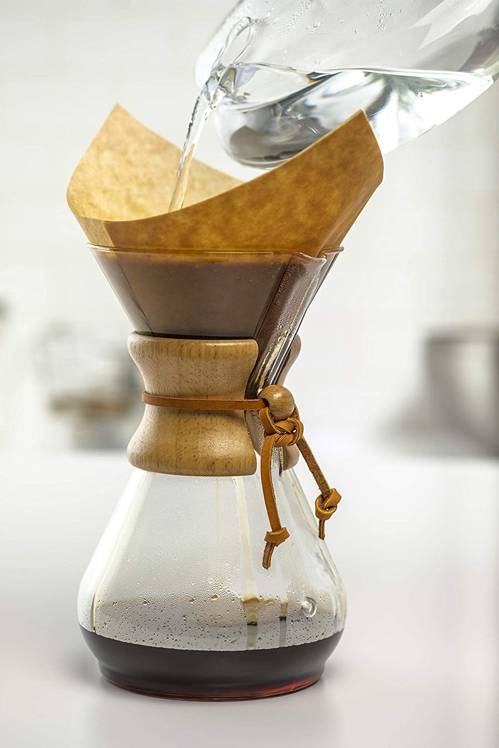 Someone pouring water in the glass coffee maker which has a wooden cuff