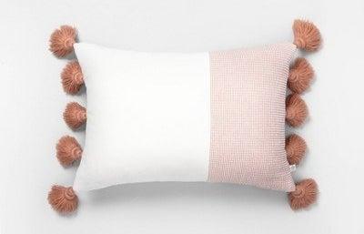 The white and auburn tasseled pillow