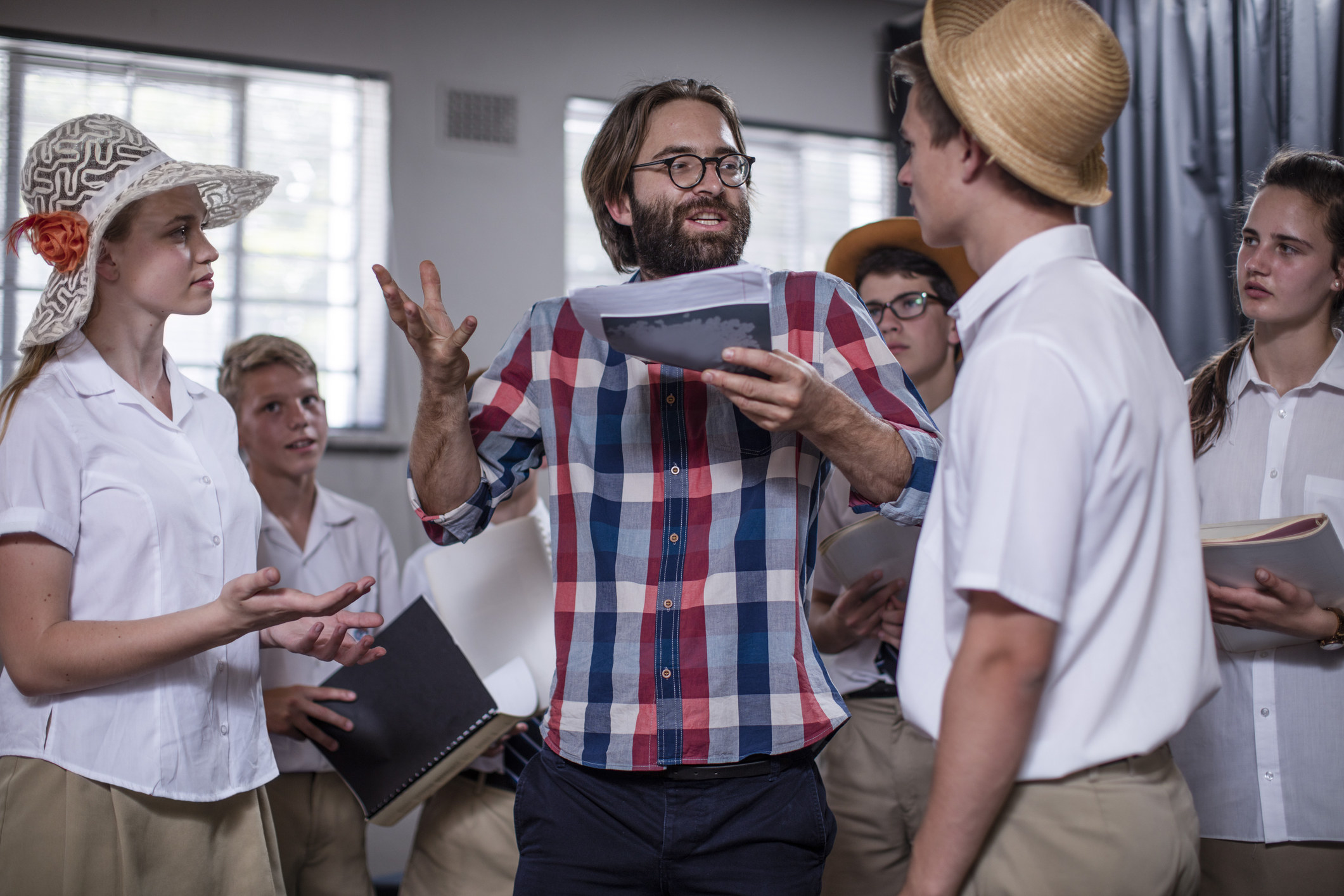 A theater teacher directing students in a play