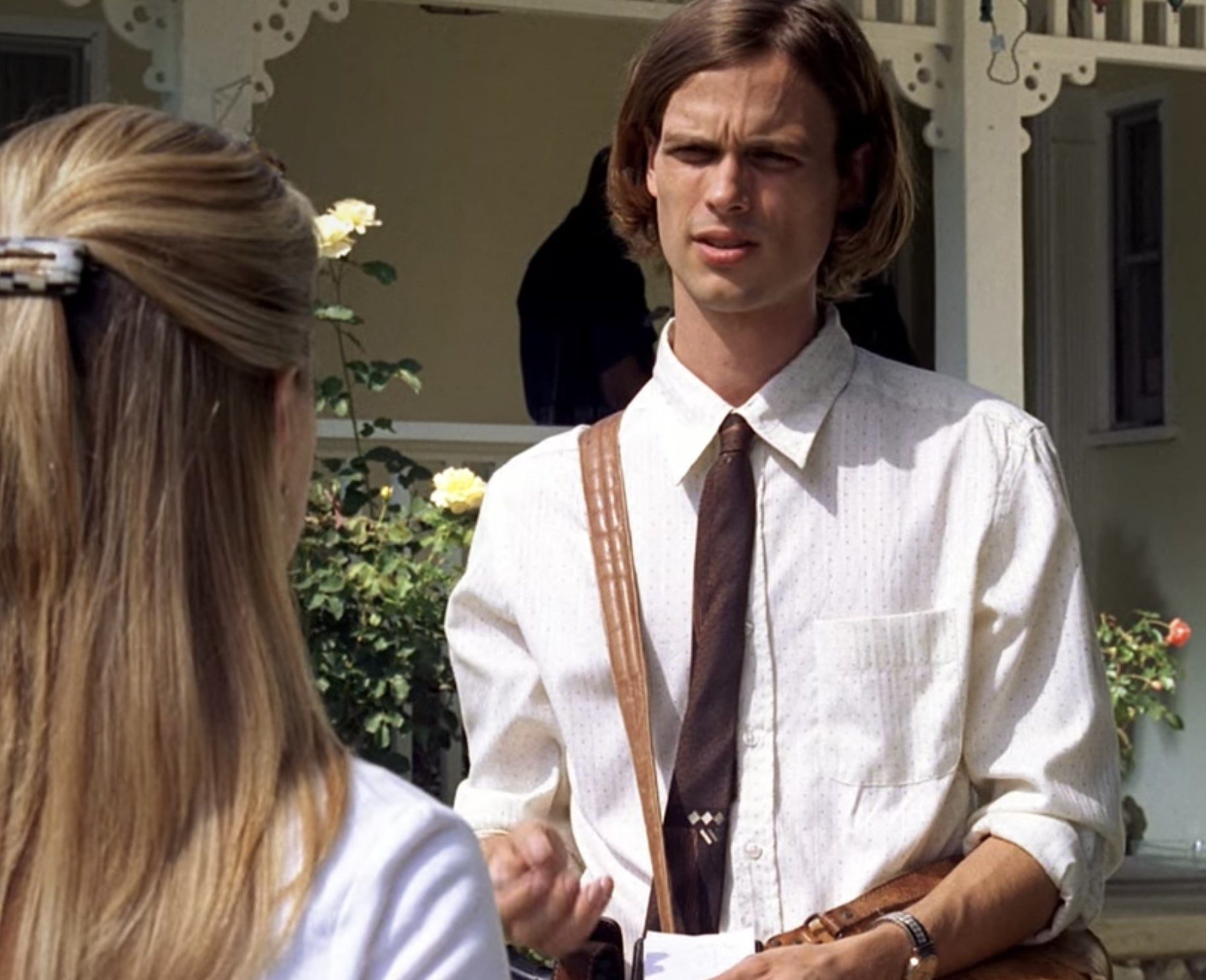 Spencer Reid from Criminal Minds talking in front of a house