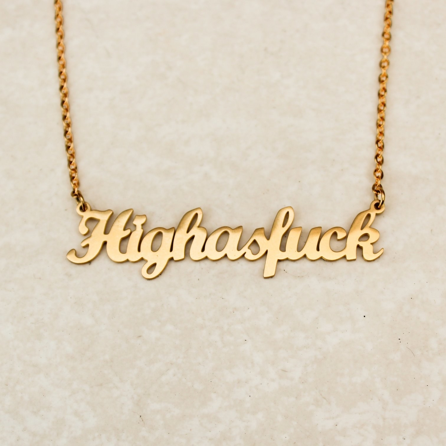 """An image of a gold necklace that says, """"Highasfuck."""""""