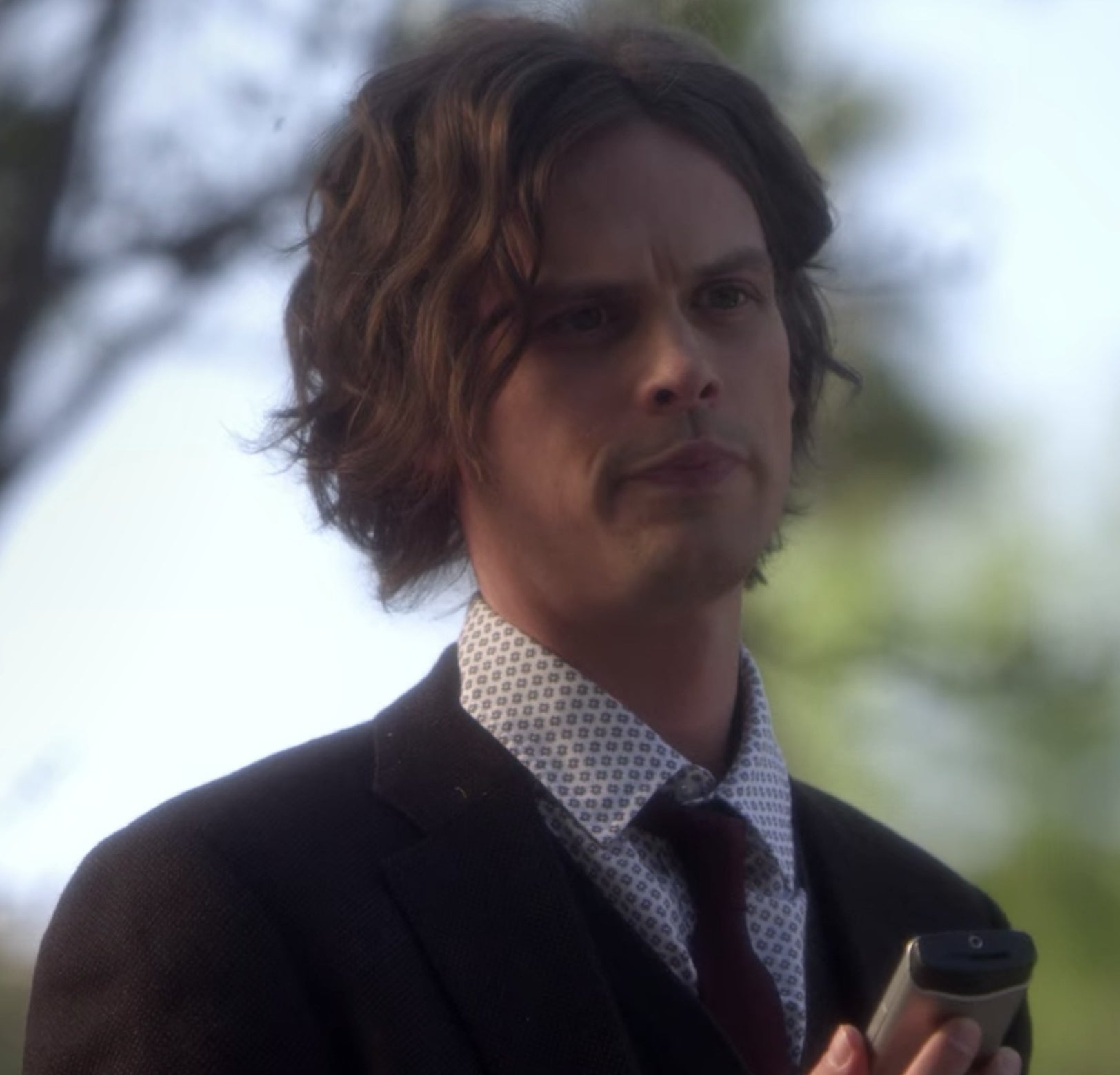 Spencer Reid from Criminal Minds talking and holding a phone