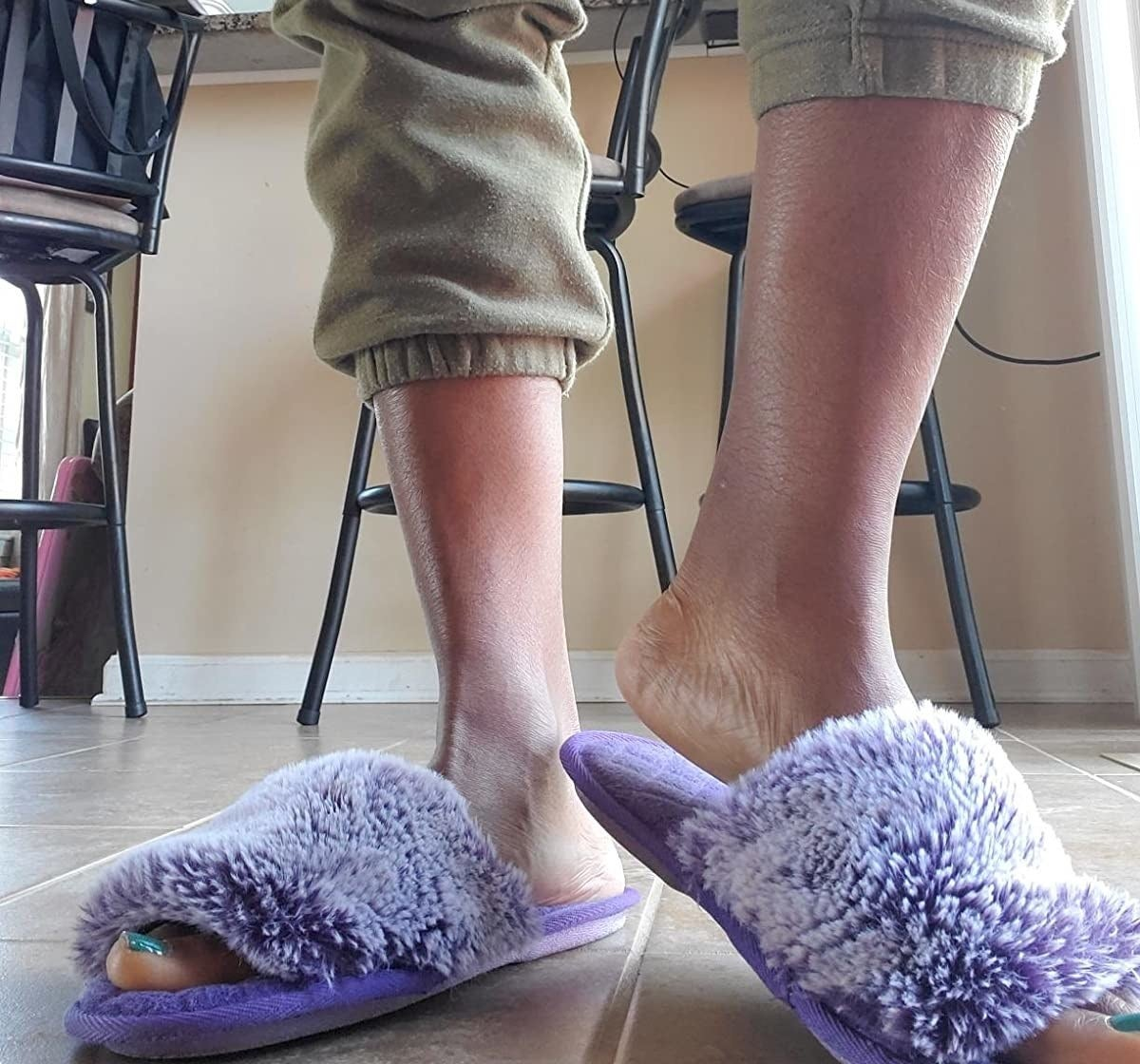reviewer wearing fuzzy slippers in purple