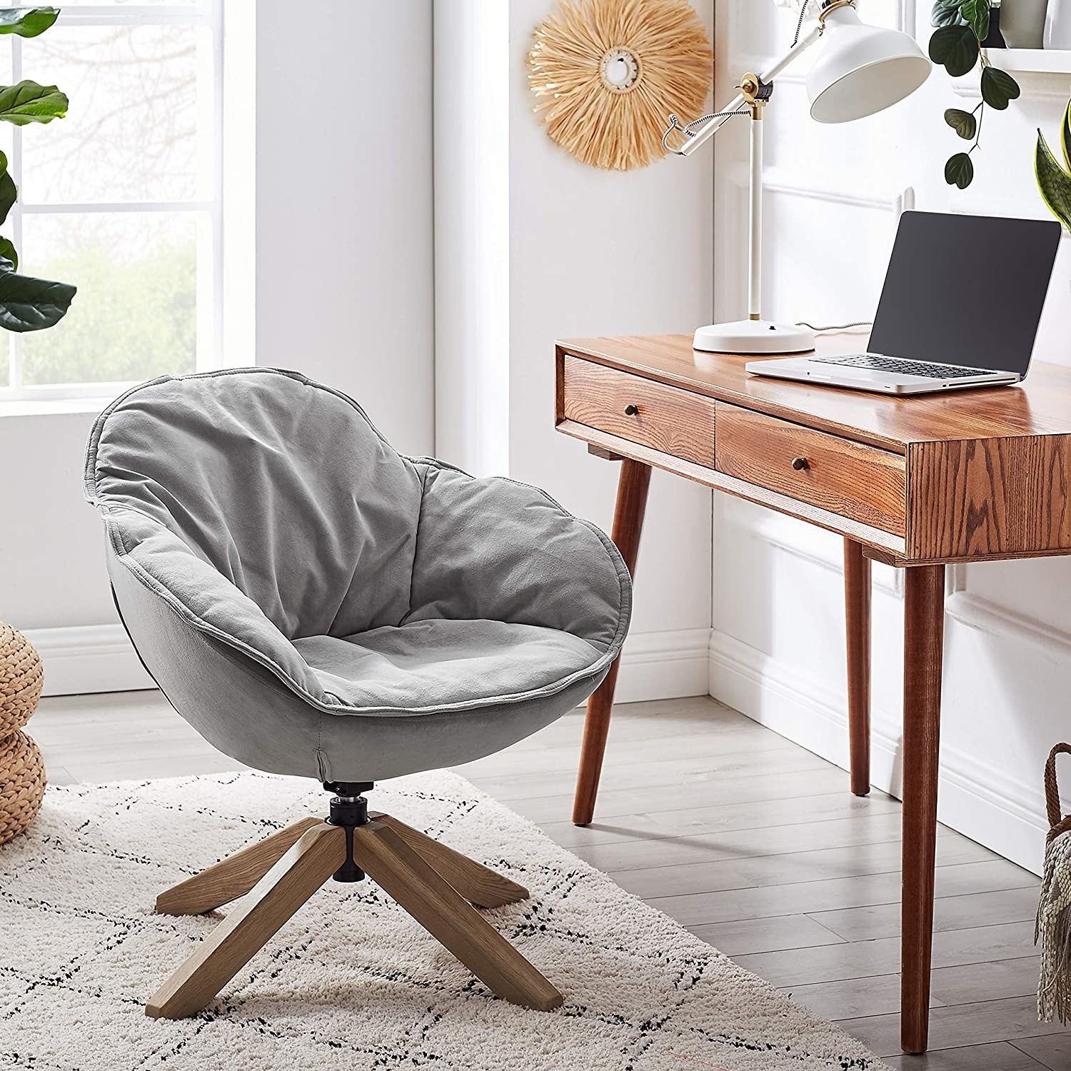 The grey velvet chair which has oak legs and the ability to swivel 360 degrees