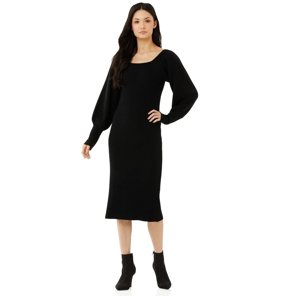 model wears puff sleeved black sweater dress with black booties