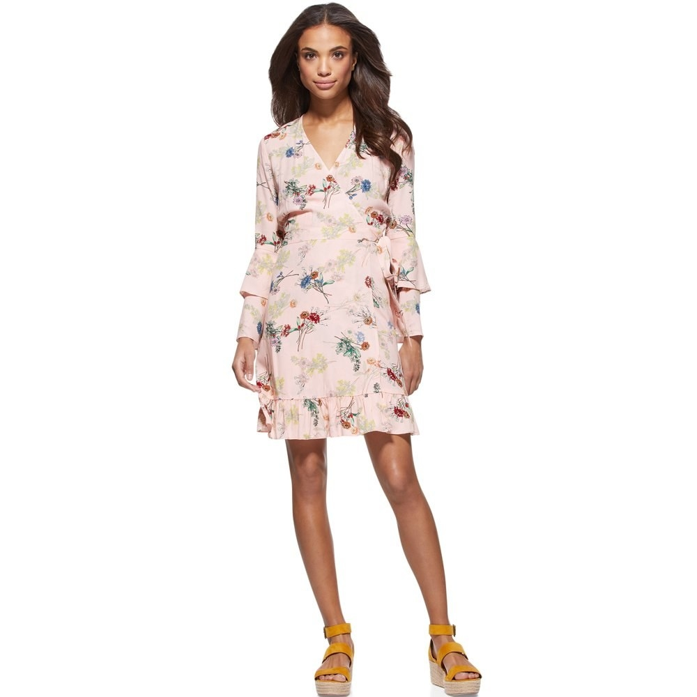 model wears pink floral wrap dress and wedges