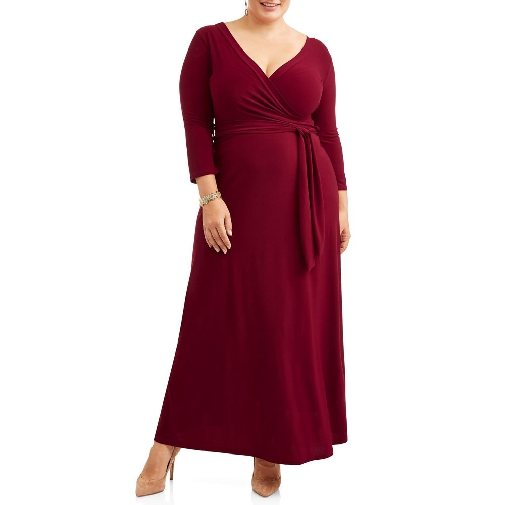 model wears wine colored maxi wrap dress  with brown heels