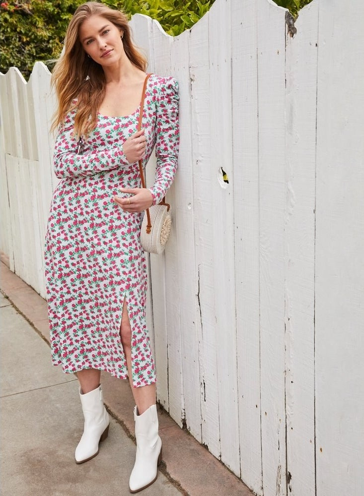 model wears printed dress with side slit and white booties