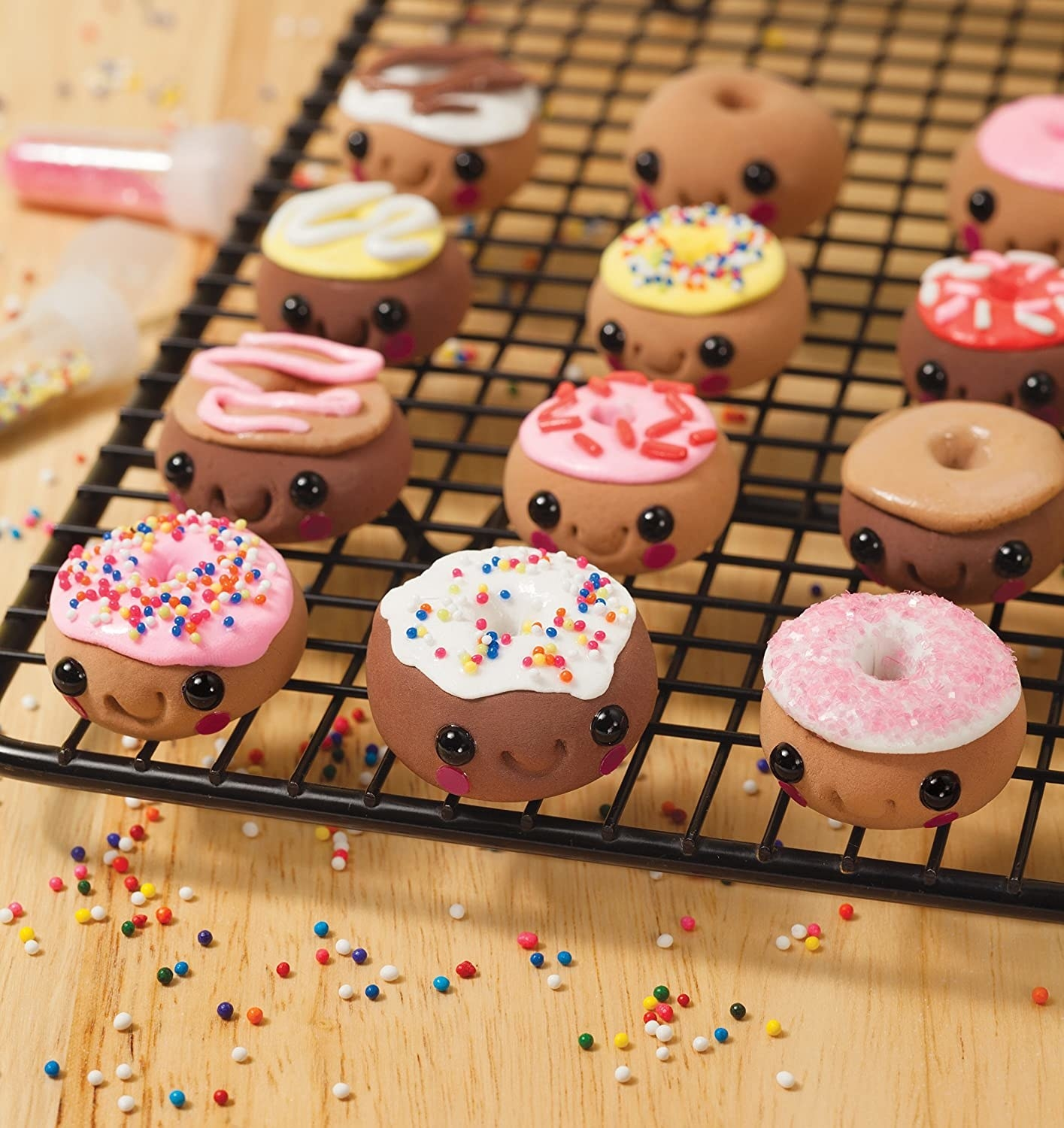 Mini clay donuts with smiling faces sitting on a cooling rack
