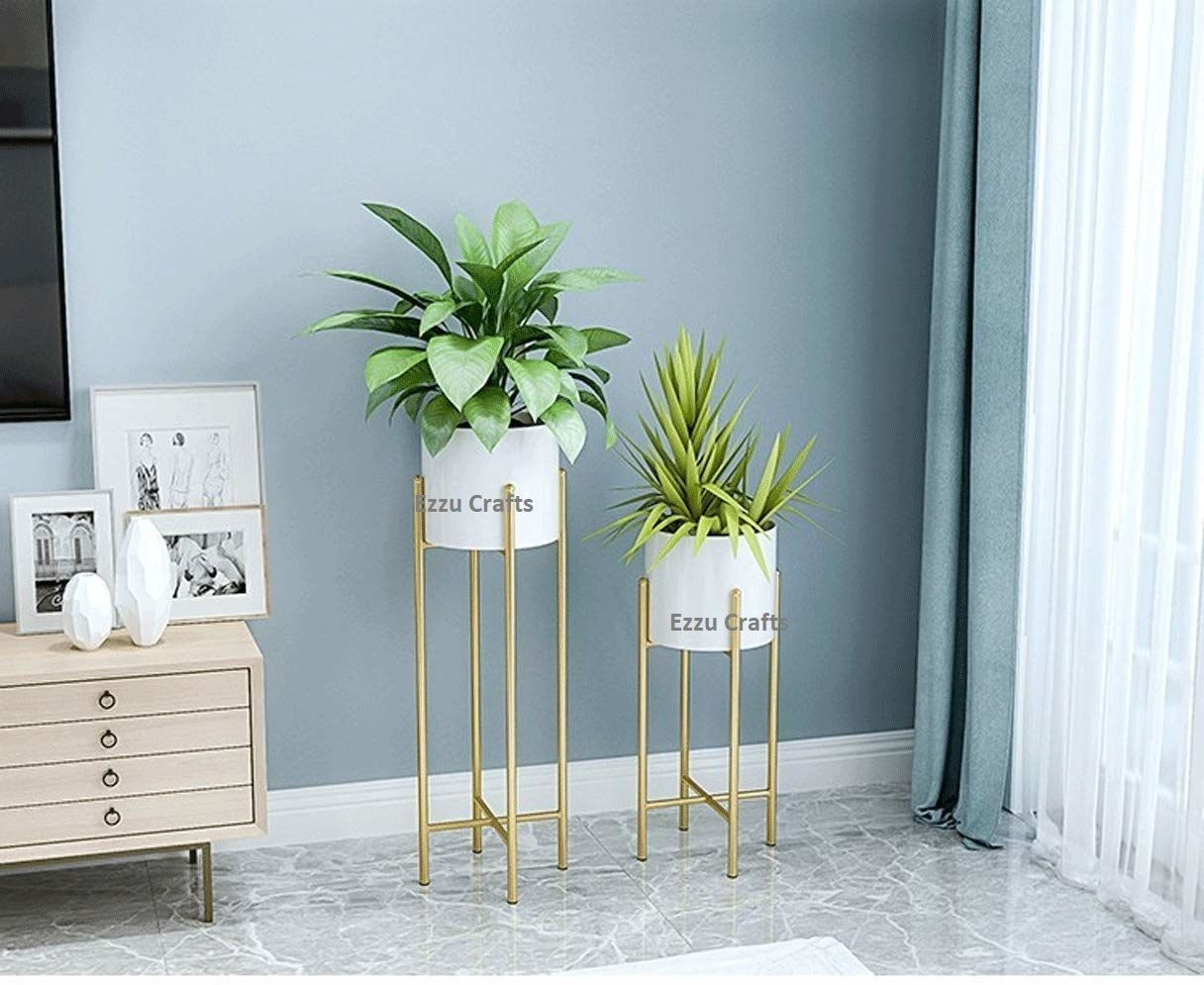 Two white round planters atop tall, gold stands.