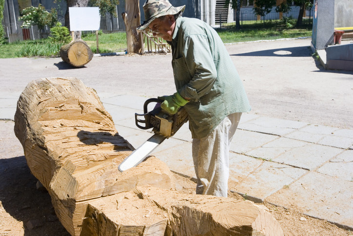 Stock photo of a man cutting wood with a chainsaw.