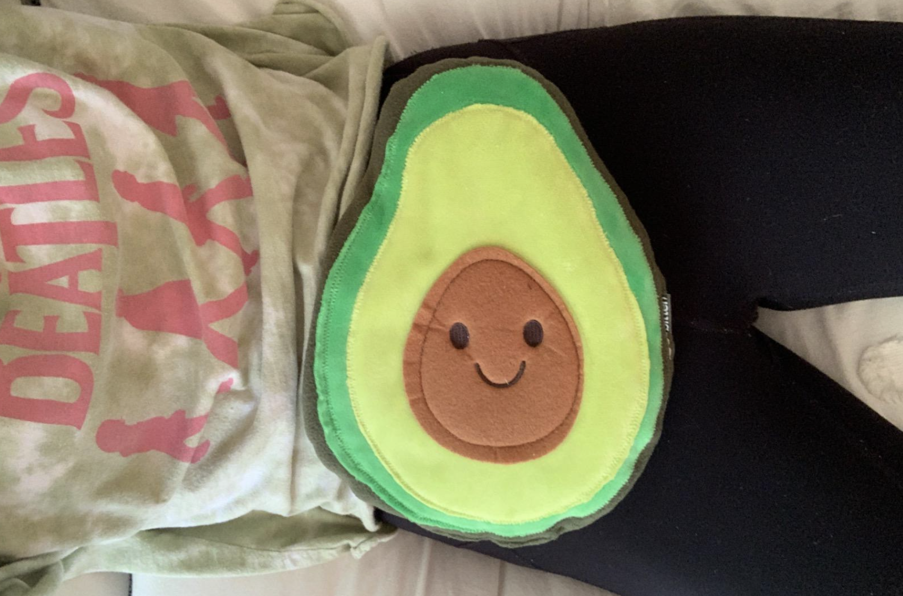 reviewer with the avocado heating pad on their lap