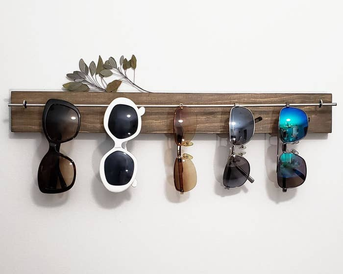 five pairs of sunglasses hanging on the sunglasses holder