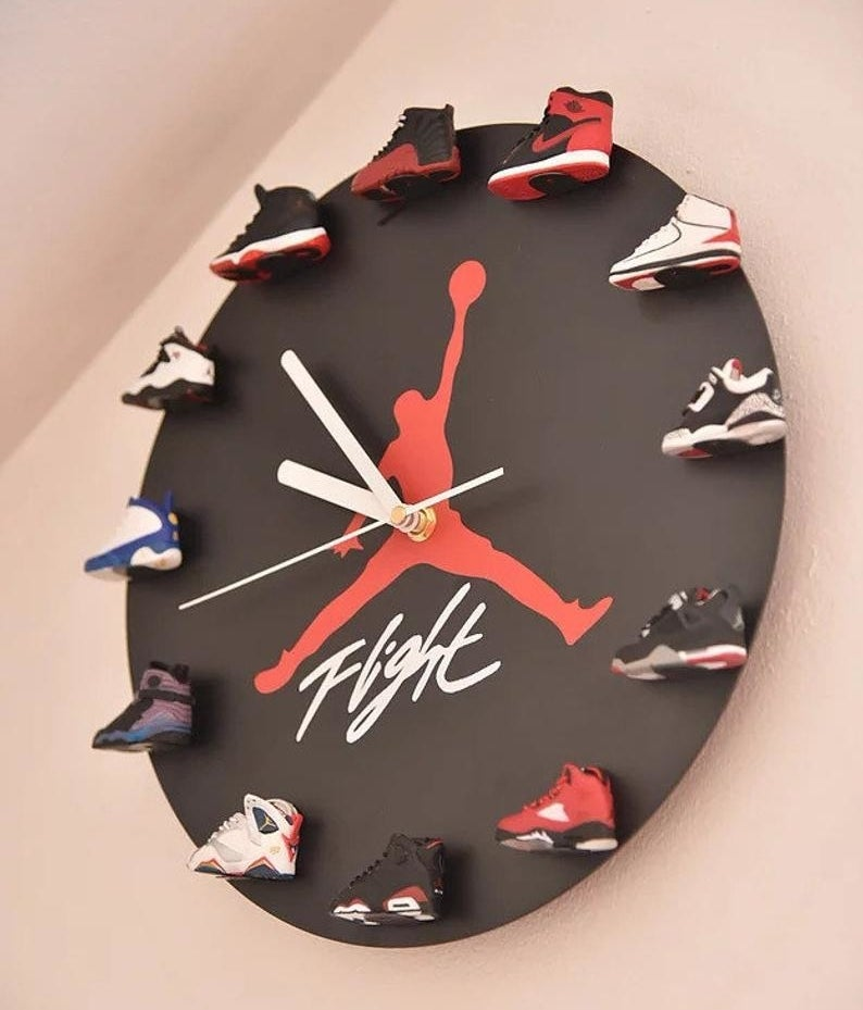 "the clock has a red jordan symbol in the middle with the word ""flight"" and 3D mini sneakers around the edge in Air Jordan numbers 1-12"