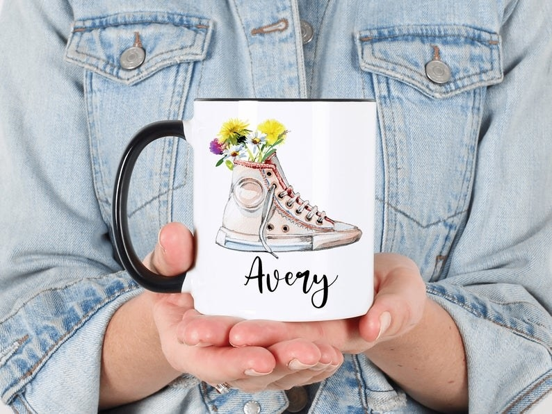 model holding the mug with a converse full of flowers on it and a name in a black cursive