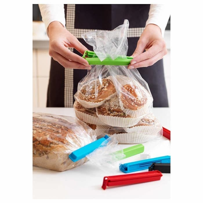 A person using the baggie seals to seal clear bags of food.