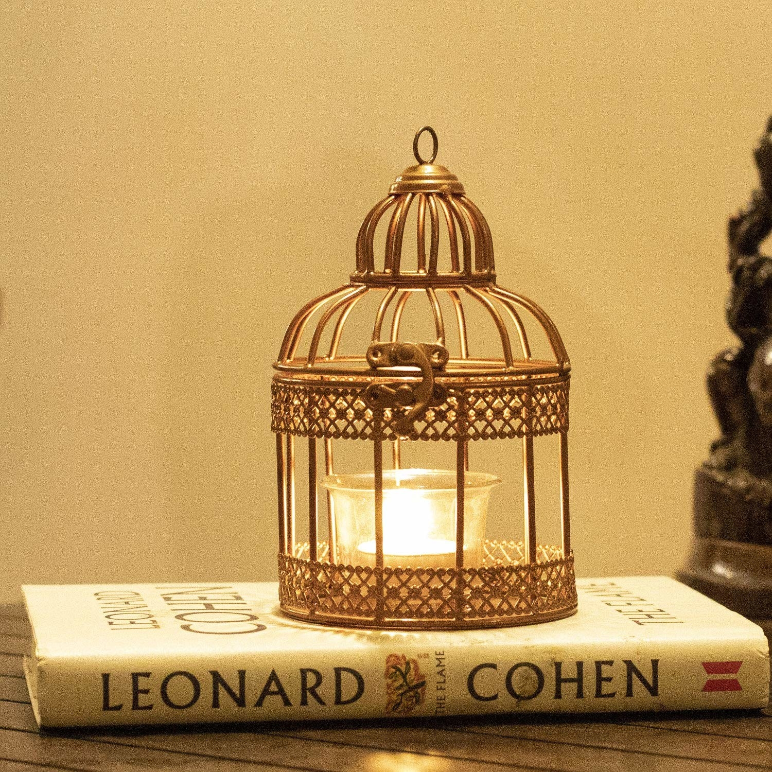 A golden bird cage on top of a book