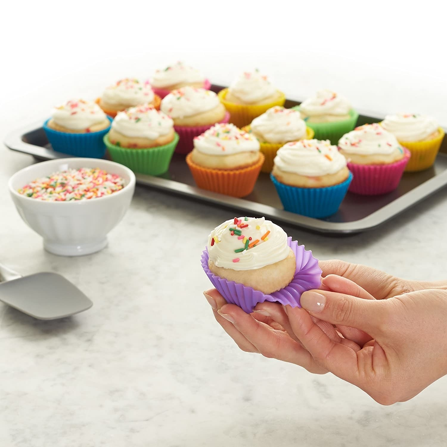 Frosted cupcakes pictured in colourful silicone cupcake moulds.