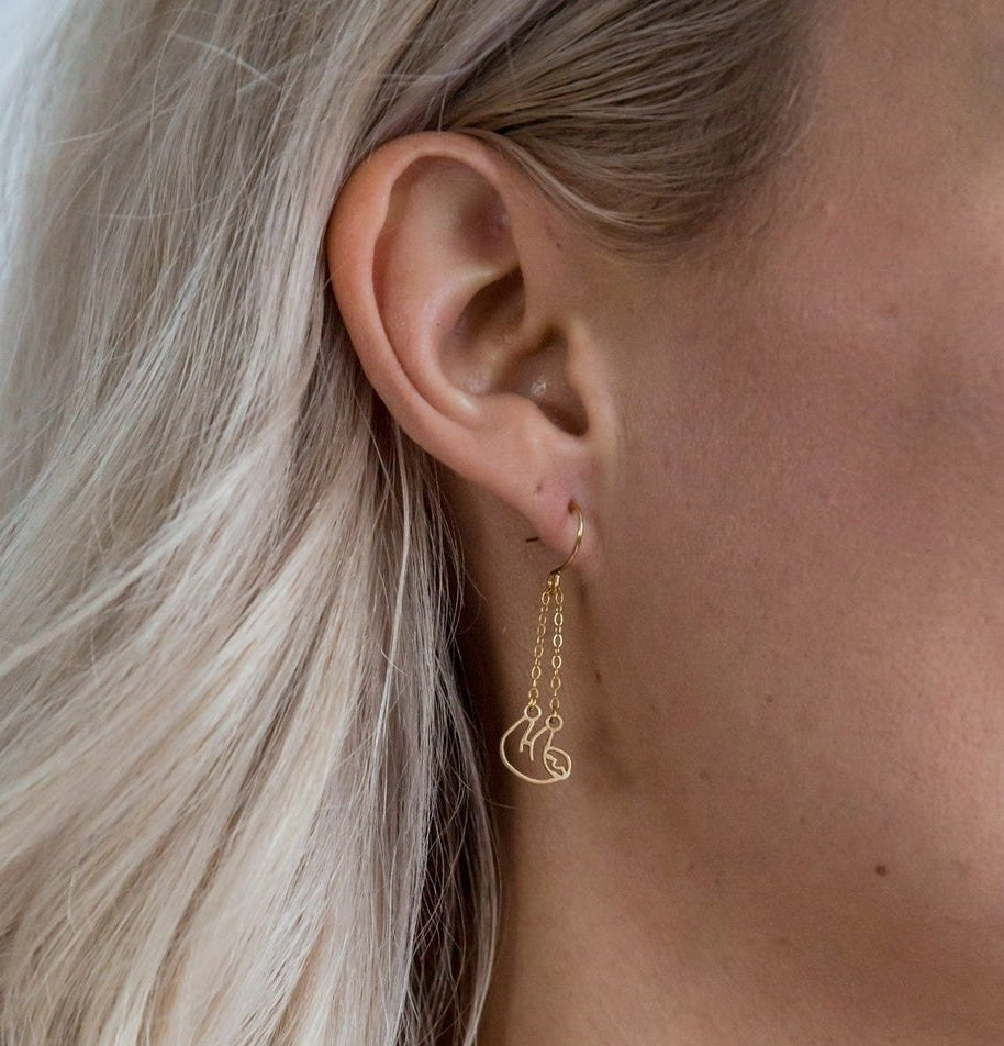 A person wearing the sloth earrings