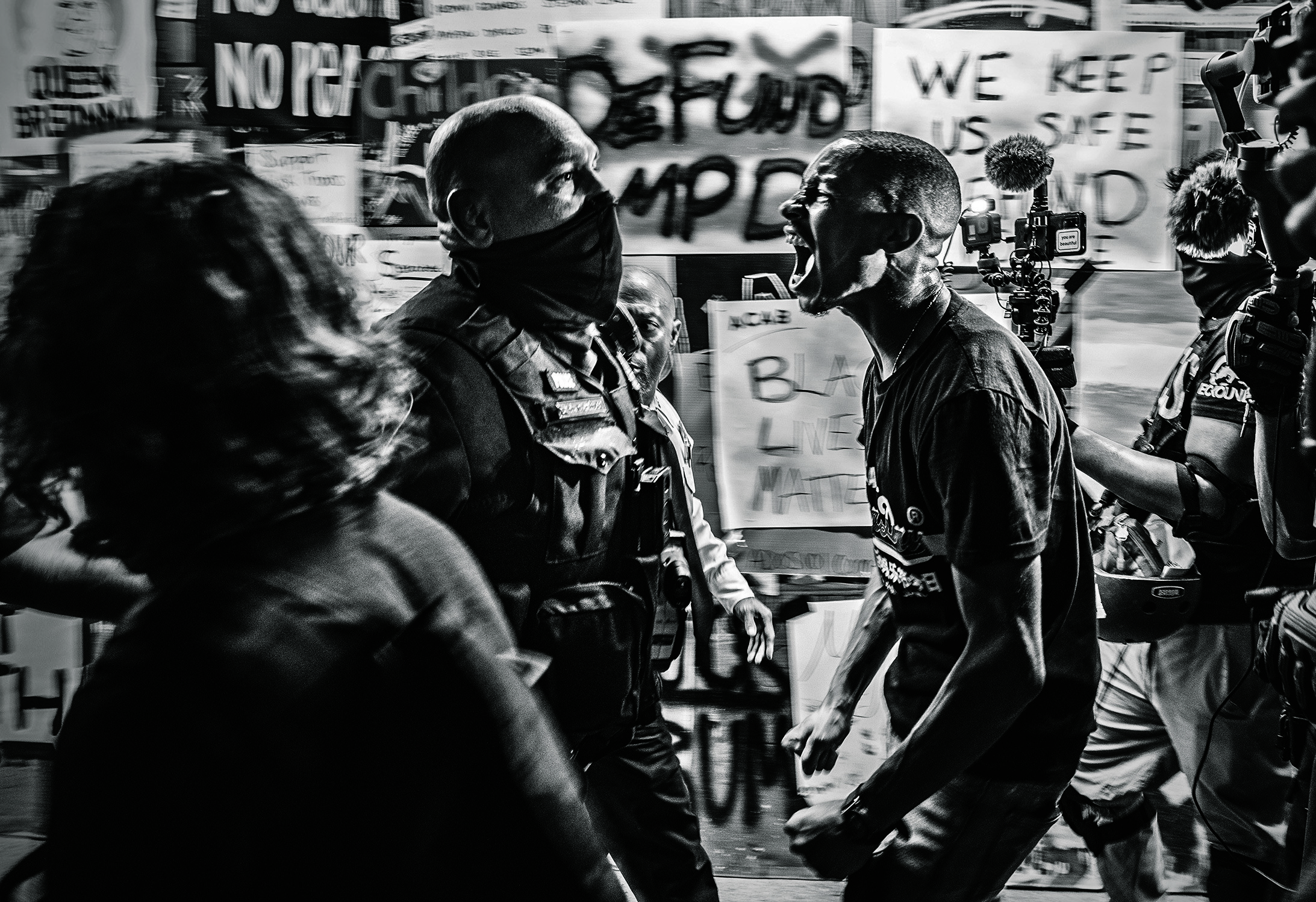 A man yells at a police officer during a protest