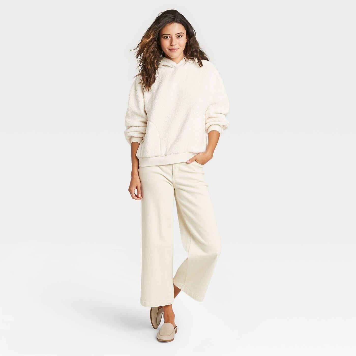 Model in cream sherpa hooded sweatshirt