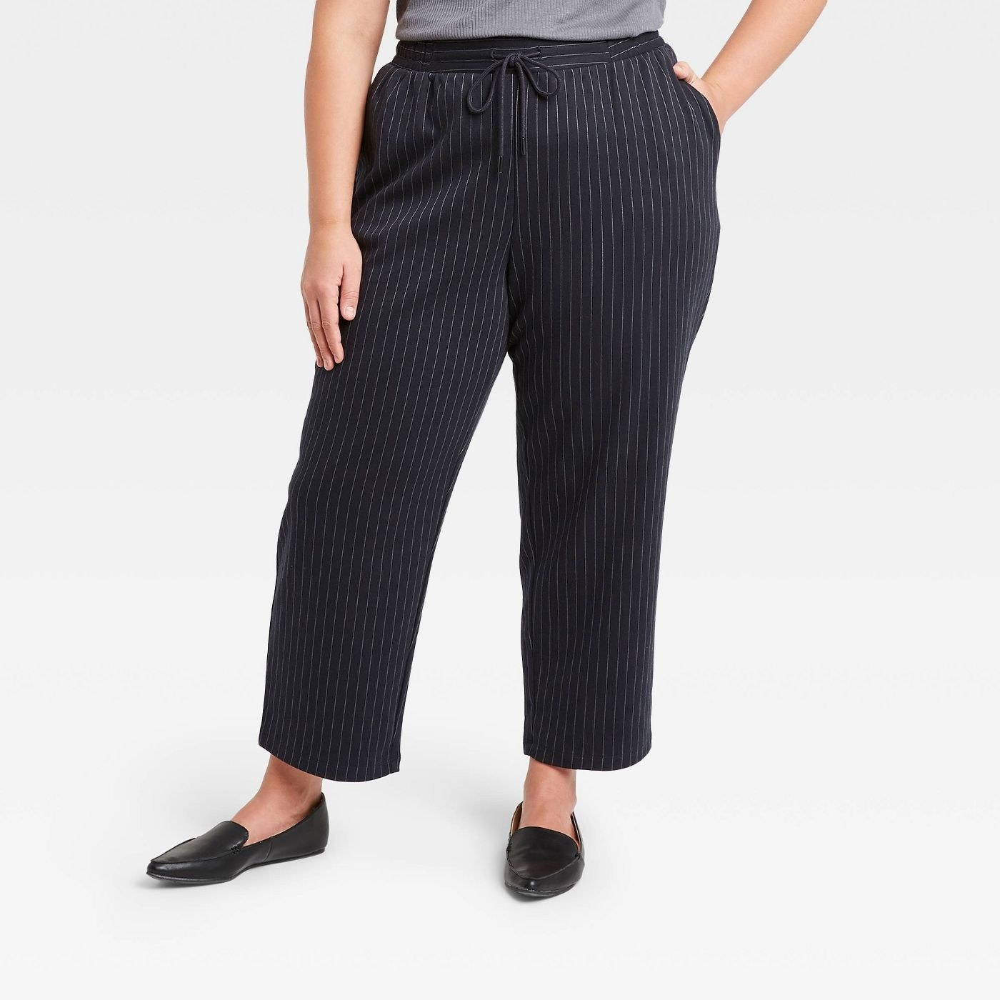 Model in pinstripe high-rise ankle knit pants