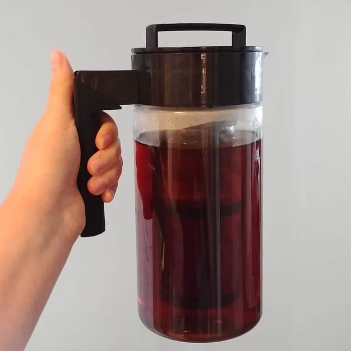 reviewer photo showing the cold brew maker being held in front of a white wall