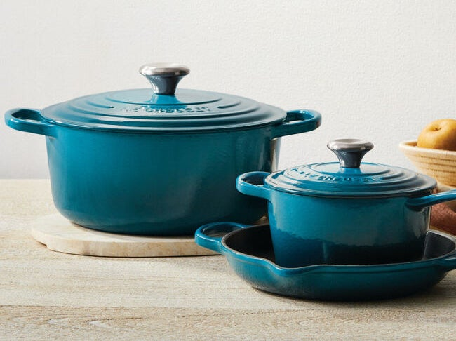 Two Dutch ovens in deep teal