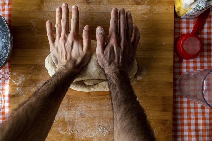 a person kneading bread dough