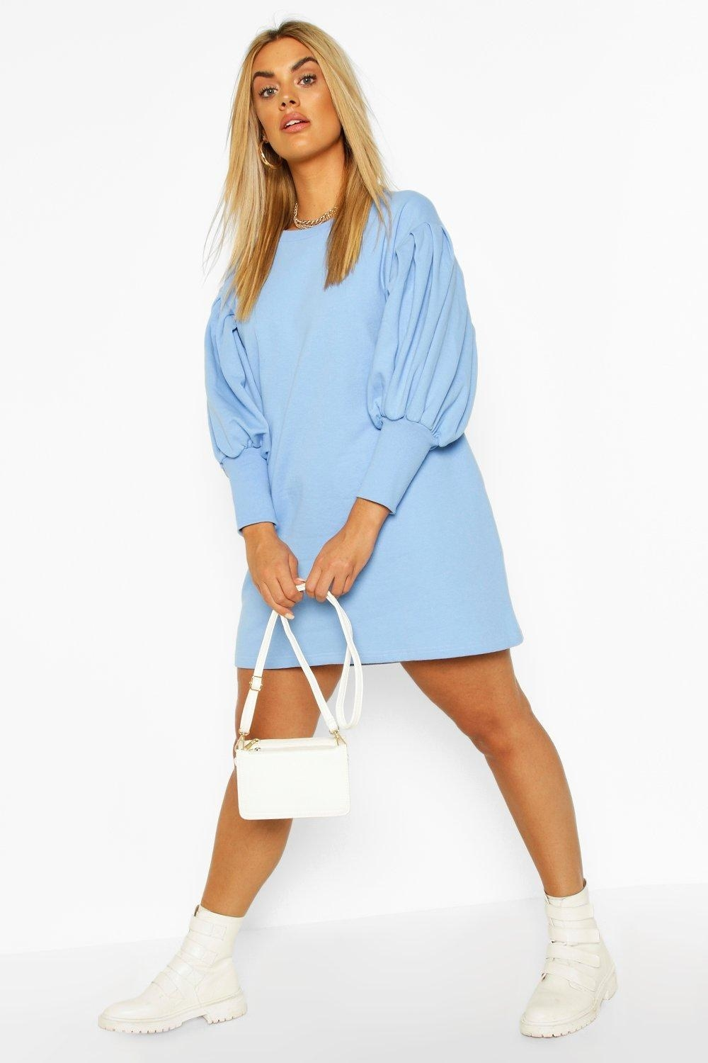 Model in the light blue crewneck dress with balloon sleeve and tight cuffs