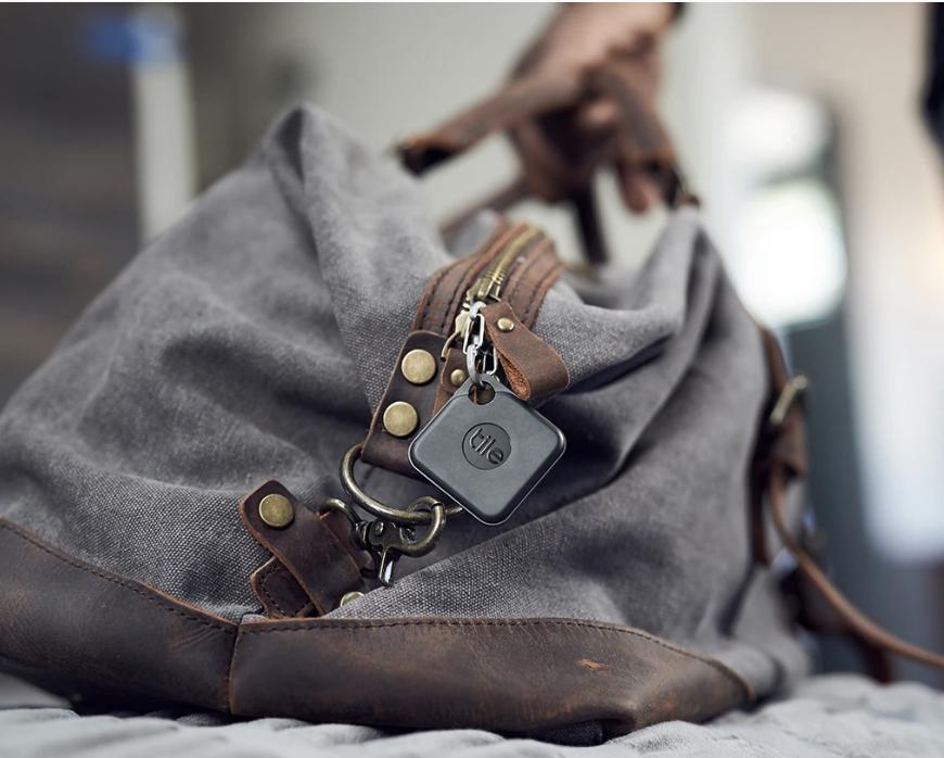 A square black Tile keychain on a handbag