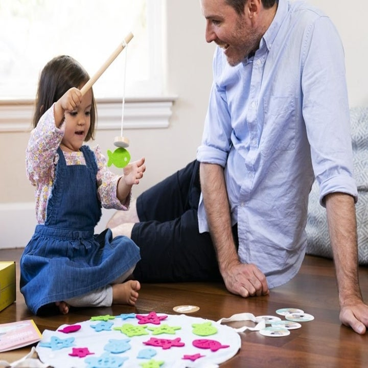 An adult model smiling down at a child model playing with an interactive indoor fishing set